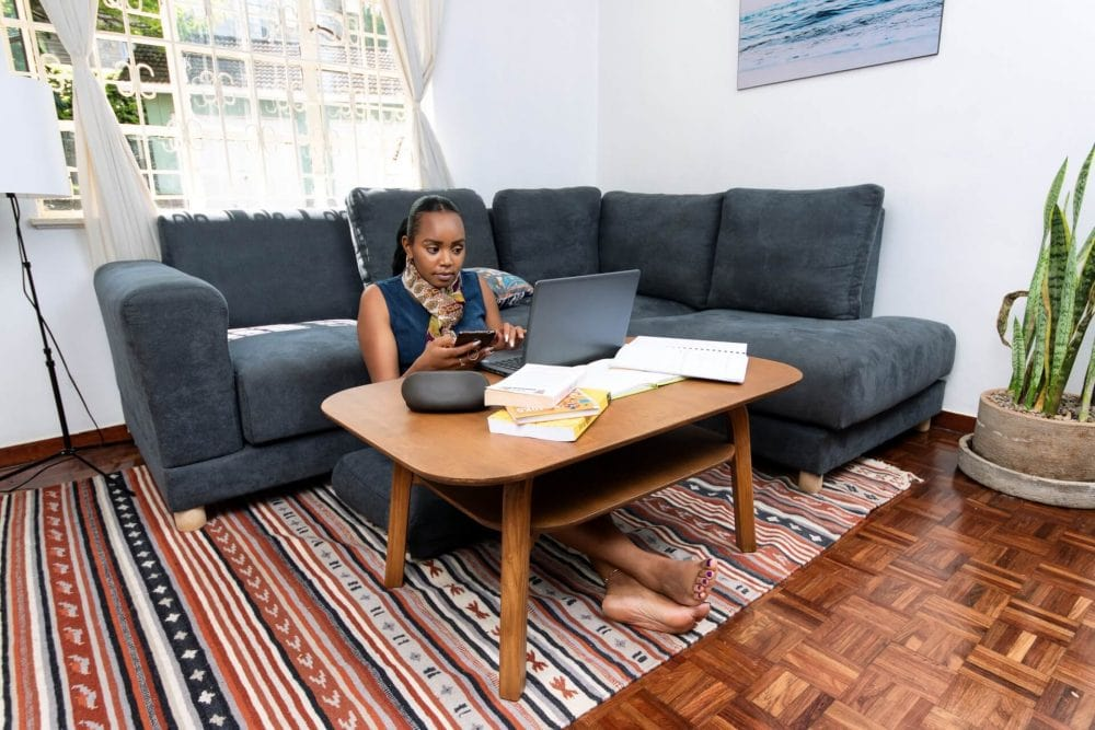 A Lady working on a Moko Coffee Table and on Moko's Jiji 5 Seater _ 6 Seater