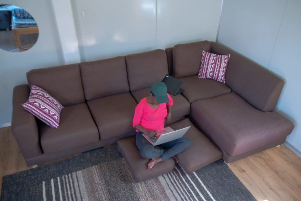 room with a 6-seater sofa and a person using their laptop