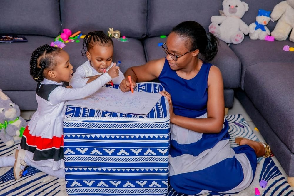 A Mother Drawing with her Children on a Moko Pouffe