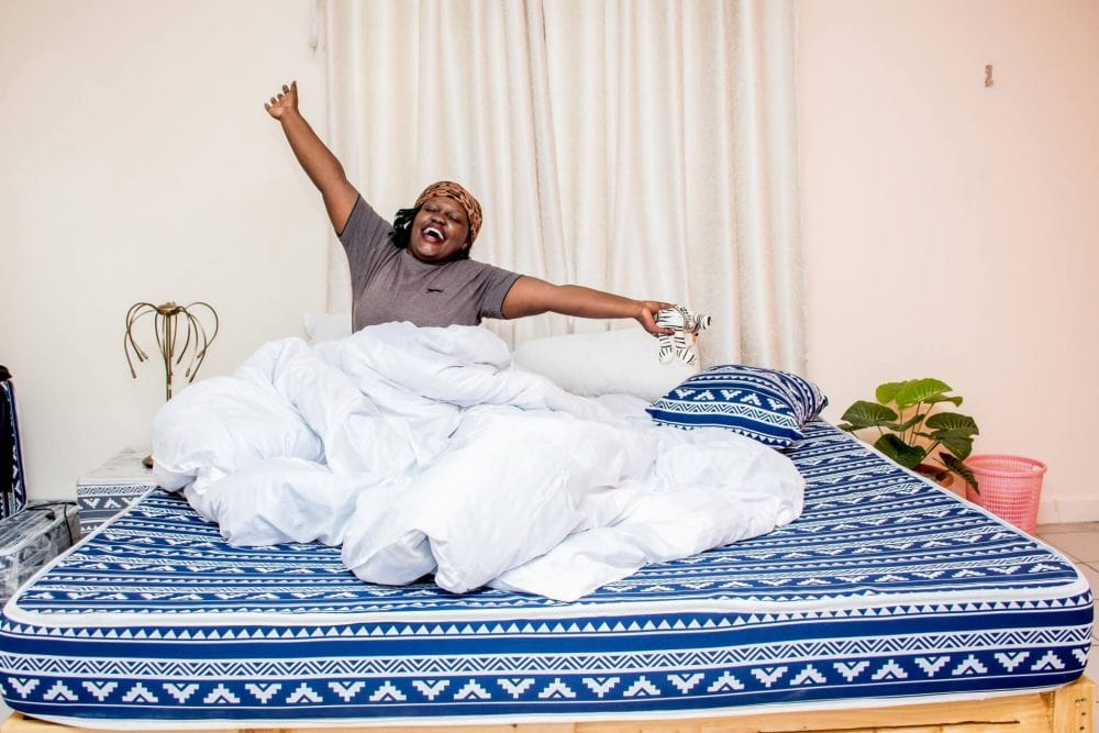 A Woman Stretching after waking up on a Moko Matress